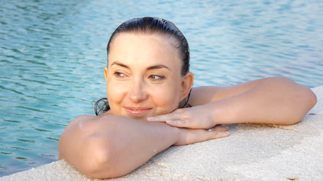 Happy caucasian woman enjoying water on the edge of the pool video