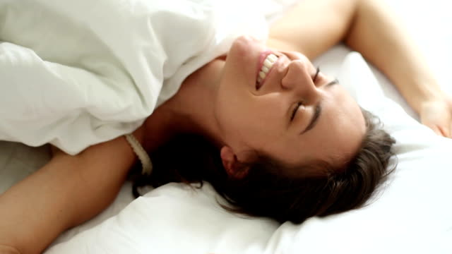 Happy caucasian woman in white clean bedding video