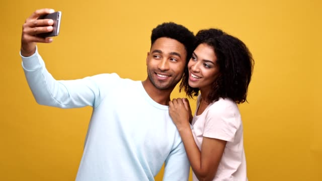 Happy cheerful afro american couple making a selfie and watching made photos isolated over yellow backgroundHappy cheerful afro american couple making a selfie and watching made photos isolated over yellow background video