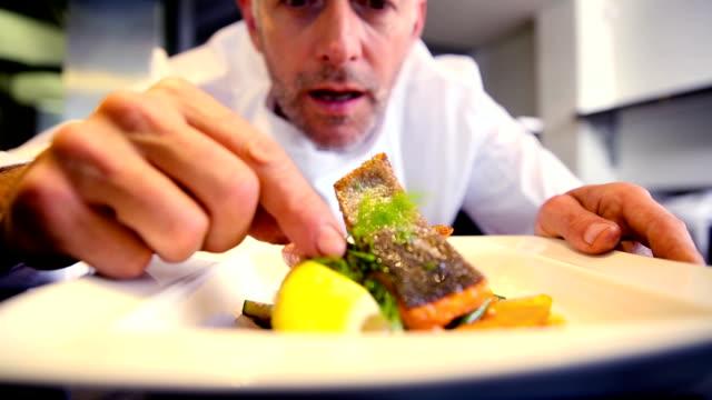 Happy chef garnishing salmon dish video