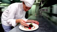 Happy chef putting mint leaf on dessert plate video