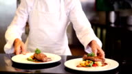 Happy chef showing two beef dishes video