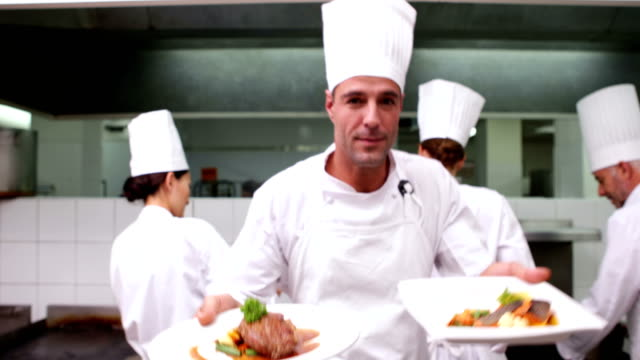 Happy chef showing two dishes to camera video