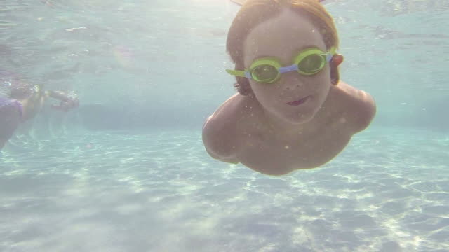 Happy child diving in a swimming pool video
