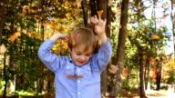 Happy child having fun with autumn leaves video