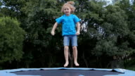 Happy child jumping on trampoline in slow motion video
