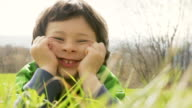 Happy child make faces lay down outdoor video HD video