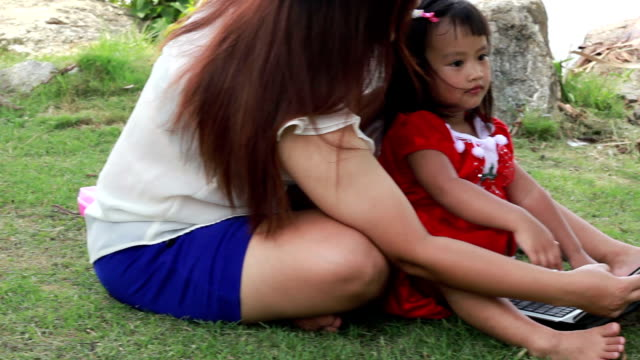 Happy child playing notebook with the mother at park video