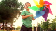 Happy child playing with pinwheel at the park video