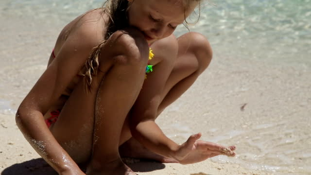 Happy child playing with sand on beach in summer video