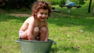 Happy child playing with water in the metallic basin video