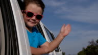 Happy child waving out of car window in slow motion video
