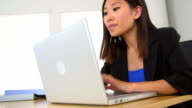 Happy Chinese businesswoman working at desk video