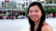 Happy chinese young woman in city center video