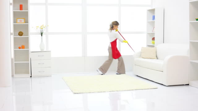 Happy cleaning lady jumping with a mop. video