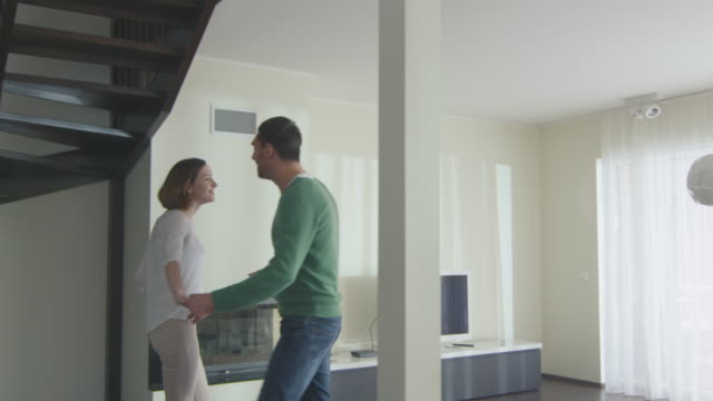 Happy couple are walking into a new home and looking around the apartment. video