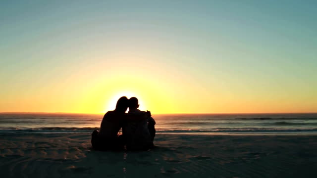 Happy couple at sunset on the beach video