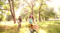 Happy couple cycling together in summer in a park video