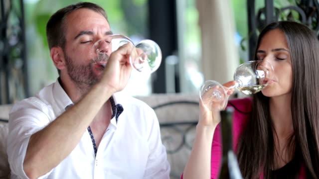 Happy couple drinking white wine in restaurant video