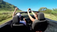 CLOSE UP: Happy couple driving in red convertible, young woman taking pictures video