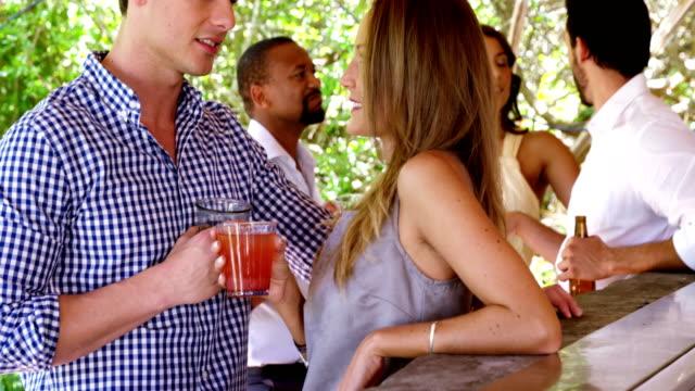 Happy couple enjoying drinks at bar counter video