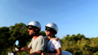 Happy couple enjoying scooter adventure whilst on holiday video