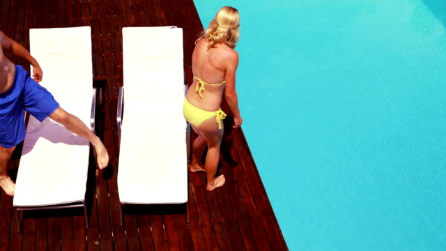 Happy couple going lying on deck chairs video