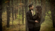 Happy couple having a date in the forest. Smiling man and woman are standing among the trees and embracing each other. Beautiful woman dressed in black dress and jacket is gently touching face video