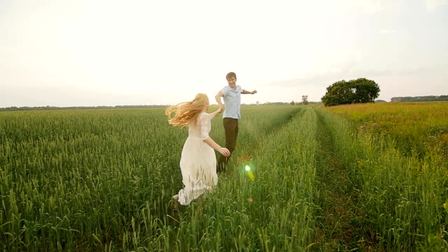 Happy couple having fun outdoors. Couple running away on the meadow. video