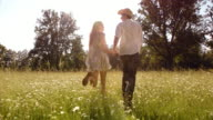 SLO MO DS Happy couple holdings hands running across meadow video