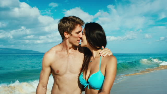 Happy couple in love playing on the beach in slow motion video