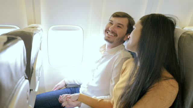 Happy couple in the plane shows a thumbs up video