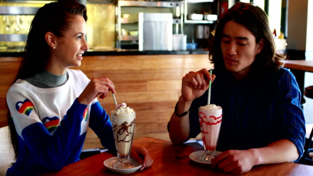 Happy couple interacting with each other while having milkshake video
