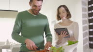 Happy couple is preparing healthy food in the kitchen at home while checking a tablet computer. video