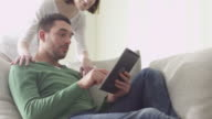 Happy couple is sitting on a sofa at home and using a tablet computer. video