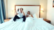 Happy couple lying in bed watching TV and use smartphone video