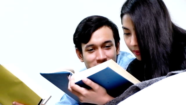 Happy couple lying on bed reading together. video