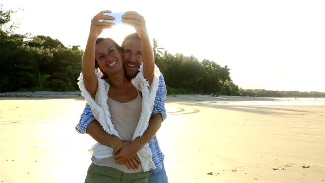 Happy couple on beach at sunset take selfie portrait video