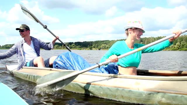 Happy couple paddling kayak, having fun. Home video, vacation video
