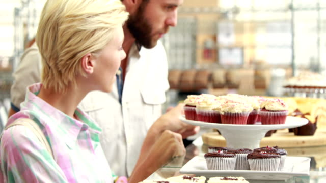 Happy couple pointing cupcakes at restaurant video