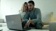 Happy couple purchasing something on internet video