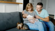 Happy couple relaxing at home with a baby in her arms, sitting beside their dog video