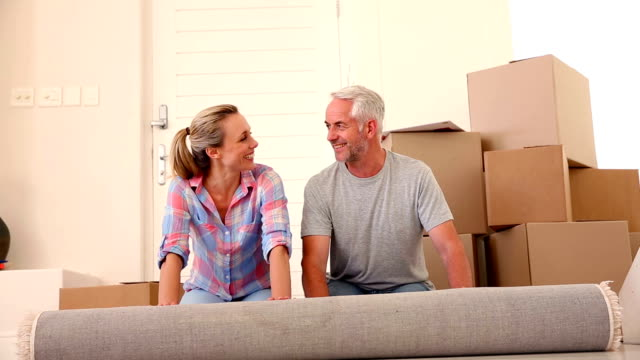 Happy couple rolling out a rug video