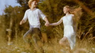 SLO MO TS Happy couple running across meadow in sunshine video