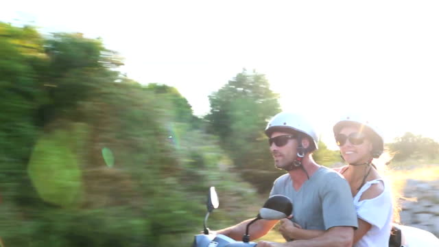 Happy couple scooter adventure in golden evening sunlight video