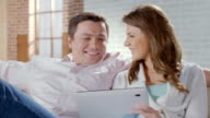 Happy couple sitting on couch with tablet pc. Online shopping video