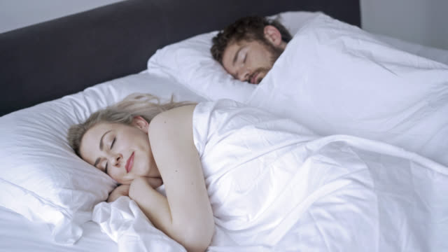 Happy couple sleeping pleasantly in their bed video