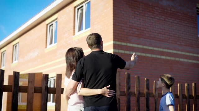 Happy couple standing outside embracing and looking at new fenced apartment. Loving family in summer sunny day showing boy modern house. Mother father and son building with three windows video