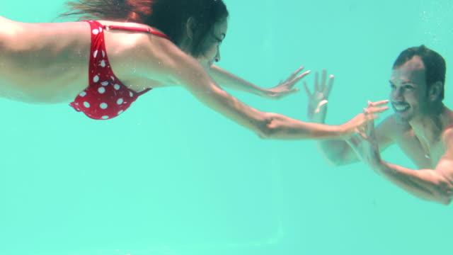 Happy couple swimming underwater video