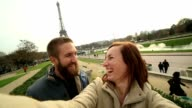 Happy couple taking selfie at the Eiffel Tower, Paris video